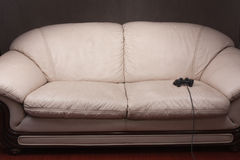 Empty couch with game controller. Empty couch with a video game controller on gray background Stock Photos