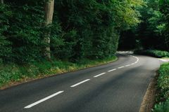 Empty country asphalt curvy road passing through the green forest in the region of Normandy, France. Nature, countryside Royalty Free Stock Image