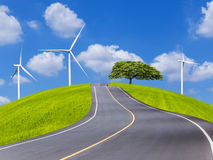 Empty country asphalt road with big tree and wind turbines Stock Image