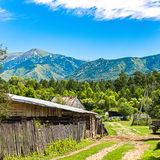 Empty country road along the fence, a barn and houses Royalty Free Stock Photo