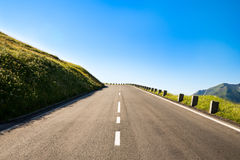 Empty country road. With a sharp left curve in the brow of a hill in the mountainous area Stock Photography