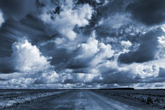 Empty country road under dramatic cloudy sky. Empty asphalt country road under dark dramatic cloudy sky royalty free stock photography