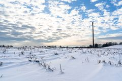 Empty Countryside Landscape in Sunny Winter Day with Snow Covering the Ground with Power Lines in Frame, Abstract Background with. Deep Look - Concept of Fun royalty free stock photo