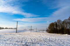 Empty Countryside Landscape in Sunny Winter Day with Snow Covering the Ground with Power Lines in Frame, Abstract Background. Concept of Fun and Joy stock photo