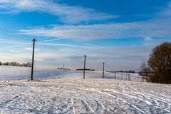 Empty Countryside Landscape in Sunny Winter Day with Snow Covering the Ground with Power Lines in Frame, Abstract Background. Concept of Fun and Joy stock photography