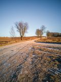 Empty Countryside Landscape in Sunny Winter Day with Snow Partly Covering the Ground, Road in the Middle of Photo - Concept of. Peace and Harmony, Vintage Film royalty free stock photography