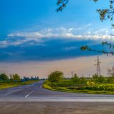 An empty crossroads near Kikinda, Serbia. Lonely cyclist in an empty crossroads with blue sky and clouds near Kikinda, Serbia Royalty Free Stock Image