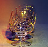 Empty crystal glasses in colored light toning Stock Photos
