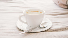 Empty cup on bed. royalty free stock images