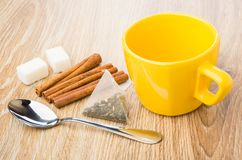 Empty cup, cinnamon sticks, teaspoon, tea bag, lumpy sugar. On wooden table Stock Images