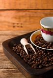 Empty cup and coffee beans in wooden tray Stock Image