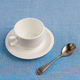 Empty cup of coffee. An empty cup of coffee on blue Scots fabric Royalty Free Stock Image