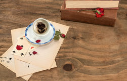 Empty cup with coffee grounds. Into a heart shape , dried rose petals,playing cards red pen on sheets of notebook paper stock photography