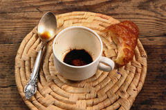 Empty cup of coffee with spoon and unfinished croissant. On wicker background Royalty Free Stock Image