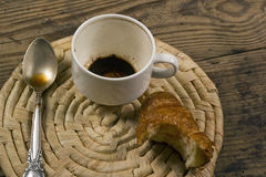 Empty cup of coffee teaspoon and unfinished croissant. On wicker background Stock Image
