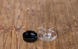 Empty cup with dish and ashtray on wooden texture Royalty Free Stock Photo