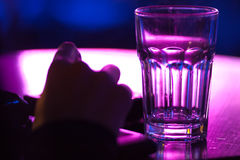 Hand with empty glass. Hand on table with empty glass, purple toned background Royalty Free Stock Images