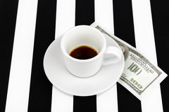 Empty cup with one hundred dollars as a tip on a black and white Royalty Free Stock Photo