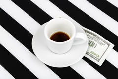 Empty cup with one hundred dollars as a tip on a black and white Royalty Free Stock Image