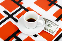 Empty cup with one hundred dollars as a tip on a red and black a Royalty Free Stock Photo