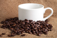 Empty cup and roasted coffee beans on sackcloth Royalty Free Stock Images
