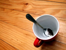 Empty cup and spoon. An empty red cup and a spoon stock images