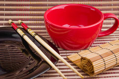 Empty cup and sushi chopsticks on a empty plate. Empty cup and sushi chopsticks on a plate Stock Photos
