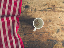 Empty cup and tea towel on wooden table Stock Photography