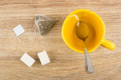 Empty cup, teaspoon, tea bag, lumpy sugar on wooden table Royalty Free Stock Image