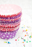 Empty cupcake cups and color sprinkles Stock Photos