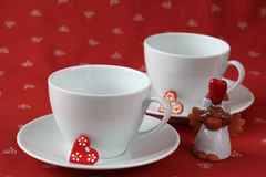 Empty cups with hearts and angel Royalty Free Stock Photo