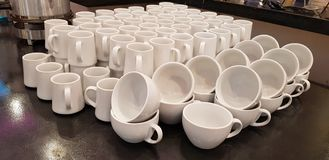 Empty white cups and mugs stacked in rows on the table stock photos