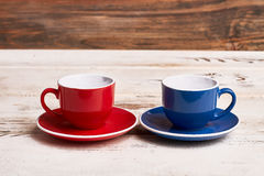 Empty cups on wooden background. Red and blue mugs. Invite friend for tea Royalty Free Stock Photo