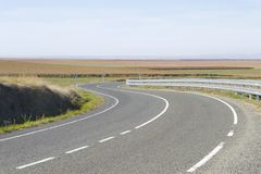 Empty curve road in a sunny day. Royalty Free Stock Photos