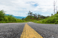 Empty curved asphalt road on green forest on mountain with cloud sky Royalty Free Stock Photo