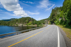 Empty curved road on the lake's shore in Norway stock photos