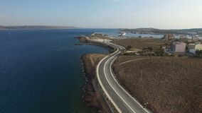 Empty curvy highway with lone cars passing along the shore of Aegean Sea. Flight over empty curvy highway with lone cars passing along the shore of Aegean Sea stock video footage