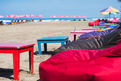 Empty cushioned chairs and loungers on the beach Stock Image