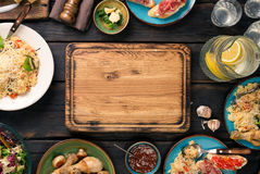 Empty cutting board on dark wooden table with variety food Stock Images