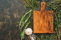 An empty cutting board with a frame of fresh herbs of thyme and rosemary. Top view, space for text or menu. stock photography