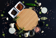 Empty cutting board and pepper, bay leaf, rosemary, onions, Himalayan salt, olive oil, soy sauce on a black backg Stock Photography