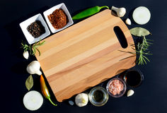 Empty cutting board and pepper, bay leaf, rosemary, onions, Himalayan salt, olive oil, soy sauce on a black backg Royalty Free Stock Photography