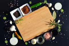 Empty cutting board and pepper, bay leaf, rosemary, onions, Himalayan salt, olive oil, soy sauce on a black backg Stock Image
