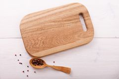 Empty cutting board, spices on white wooden table Royalty Free Stock Photography