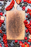 Empty cutting board and various berries Royalty Free Stock Images