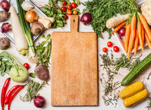 Empty cutting board and various raw vegetables for tasty and healthy cooking, top view, place for text, Royalty Free Stock Photos