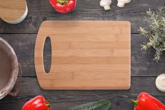 Empty cutting board on wooden desk surrounded with vegetables, mushrooms, spice box, plant, milk bucket Royalty Free Stock Photography