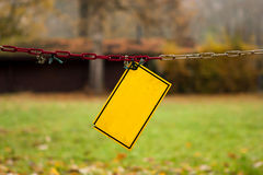 Empty, damaged yellow warning sign hanging on a dirty chain in the park Royalty Free Stock Photography