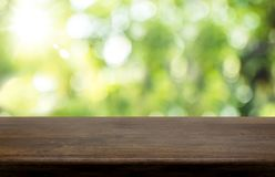 Empty dark brown hard wood table top with sun and blur green tre Stock Image