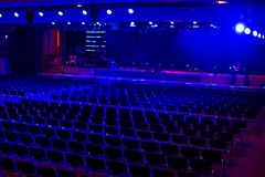Empty dark Modern hall for events and presentation with stage and blue light. Preperation for ceremony in process. Selective focus royalty free stock photography